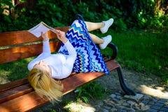 妇女花费与书的休闲 自我改善的时刻 夫人喜欢读 读的女孩户外,当放松时 库存照片