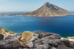 妇女草帽和太阳镜在岩石地面在卓著的自然观点的地中海希腊语泰伦佐斯岛从 库存照片