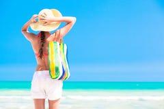 妇女草帽的和一个热带海滩的与 免版税库存图片