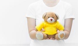妇女藏品和保护给一个棕色玩具熊玩具穿戴黄色衬衣坐白色背景特写镜头 免版税库存照片