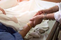 妇女藏品女孩的手热病患者在医院 免版税图库摄影