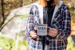 妇女藏品杯子咖啡在野营的早晨 库存图片