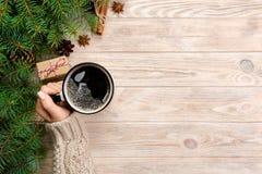 妇女藏品杯子在土气木桌上的热的咖啡 在温暖的毛线衣的手有杯子的,冬天早晨或圣诞节概念,顶面v 库存照片