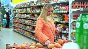 妇女藏品石榴果子,特写镜头 她选择她的晚餐的果子 股票录像
