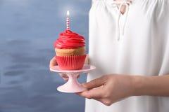 妇女藏品立场用生日杯形蛋糕 免版税库存图片