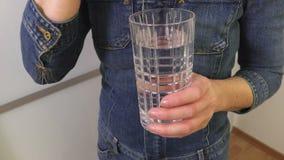 妇女藏品药片和杯水 影视素材