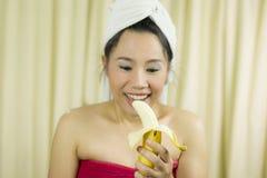 妇女藏品香蕉代理微笑,哀伤,滑稽,穿着裙子在洗涤头发以后包括她的乳房,包裹在毛巾在阵雨 免版税库存照片