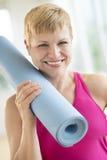 妇女藏品滚动锻炼席子在健身房 免版税库存图片