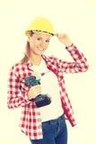 妇女藏品钻子和佩带安全帽 免版税库存照片