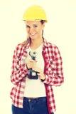 妇女藏品钻子和佩带安全帽 免版税图库摄影