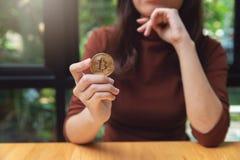 妇女藏品cryptocurrency金黄bitcoin硬币 免版税库存照片