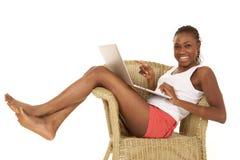 妇女藤椅膝上型计算机微笑 库存照片