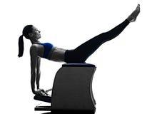 妇女行使健身被隔绝的pilates椅子 免版税库存照片