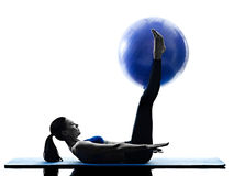 妇女行使健身被隔绝的pilates球 免版税图库摄影