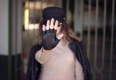 妇女街头时尚室外照片有黑发的在黑皮夹克和太阳镜在defocus 打手势中止与的妇女 库存图片