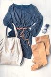 妇女衣物集合顶视图  黑色加点了礼服、褐色皮靴和辅助部件在木背景 库存图片