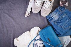 妇女衣物,辅助部件,鞋类蓝色女衬衫,牛仔裤,赤土陶器鞋子,袋子 时尚成套装备 背景袋子概念行程购物的白人妇女 顶视图 库存照片