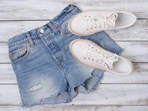 妇女衣物,鞋子白色运动鞋,牛仔布短裤 时尚成套装备,春天夏天汇集 背景袋子概念行程购物的白人妇女 平的位置,看法 库存照片