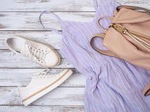 妇女衣物,鞋子,辅助部件淡紫色礼服,白革运动鞋,米黄背包 时尚成套装备,春天夏天 库存图片