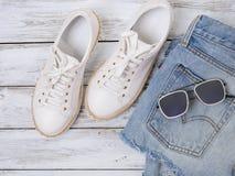 妇女衣物,鞋子,辅助部件白色运动鞋,牛仔布短裤,太阳镜 时尚成套装备,春天夏天汇集 购物 图库摄影