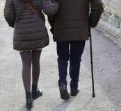 妇女补充更老的绅士以拐棍 免版税库存照片