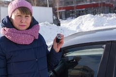 妇女被买一辆汽车在冬天 免版税图库摄影