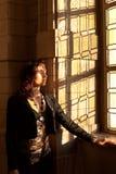 妇女被关闭注视太阳被弄脏的窗口 库存图片
