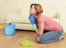 妇女被注重和疲倦清洗洗涤在她膝盖祈祷的房子地板 免版税库存图片
