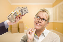 妇女被递堆金钱在空的屋子里 库存图片