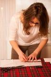 妇女裁缝切口纺织品在工艺车间 免版税图库摄影