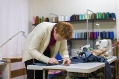妇女裁缝在一个缝合的演播室工作 库存图片