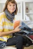 妇女装箱她的皮箱 免版税库存图片