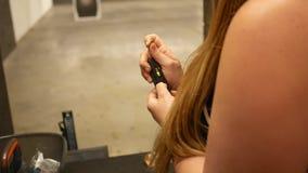 妇女装载子弹入枪夹子杂志在射击距离 股票录像