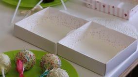 妇女装饰辫子说谎在板材的蛋糕流行音乐弓  用驱散不同颜色装饰的糖果 在gif的箱子附近 股票录像