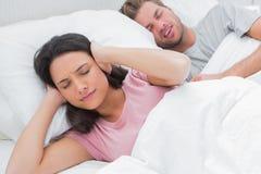 妇女覆盖物耳朵,当她的丈夫打鼾时 免版税库存照片