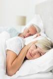 妇女覆盖物耳朵,当打鼾在床上时的人 图库摄影