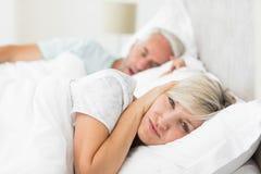 妇女覆盖物耳朵,当打鼾在床上时的人 库存图片