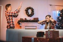 妇女覆盖物耳朵,当让党popper的人,一起时庆祝圣诞节 免版税图库摄影