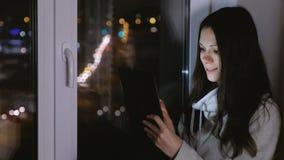 妇女观看在片剂计算机和笑上的影片 坐窗台在黑暗的夜 影视素材