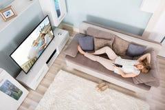 妇女观看的电视大角度看法  免版税库存图片