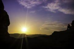 妇女观看紫色日落在自然曲拱下 免版税库存图片