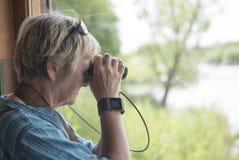 妇女观鸟看通过一台双筒望远镜 免版税库存图片