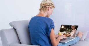 妇女视讯会议背面图在沙发的 库存照片