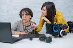 妇女视频编辑器和使用图形输入板的年轻助理 免版税图库摄影