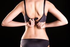 妇女解扣她的胸罩 免版税库存照片