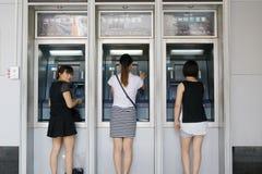 妇女让步在脊椎工业和商业银行atm  免版税库存照片