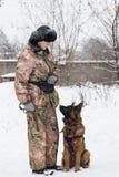 妇女训练德国牧羊犬,冬天, 免版税图库摄影