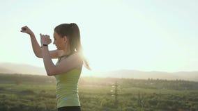 妇女训练打击的一位美丽的年轻拳击手,它是在山的背景环境美化表面上  股票录像