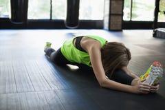 妇女训练stratching的健身房 免版税库存图片