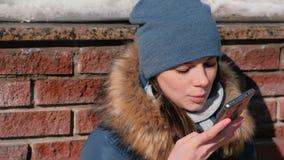 妇女讲在坐在冬天公园的手机的音频消息 特写镜头面孔正面图 股票录像